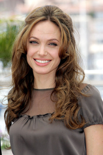 Looking very pretty in a soft gray shirt and done up hair. angelina jolie