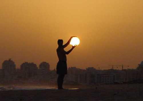 "Man ""holding"" sun"